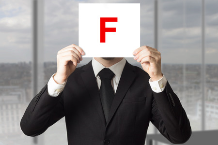 hidden success: businessman in black suit holding up sign with letter f