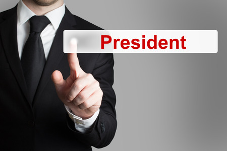 privileged: businessman in black suit pushing flat button president