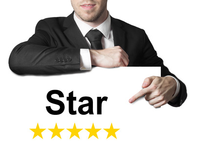 prominence: businessman in black suit pointing on white sign star golden rating vip