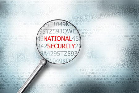 sourcecode: reading word national security on digital computer screen with a magnifying glass internet security