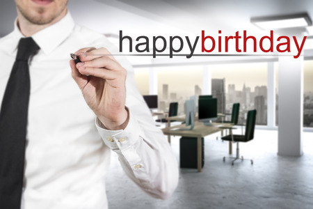 freetime: businessman  in modern office writing happy birthday in the air