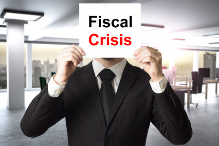 fiscal: businessman in black suit hiding face behind sign fiscal crisis