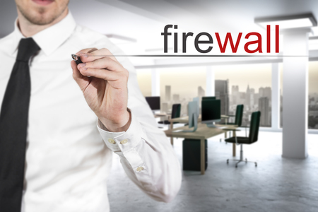 businessman in modern office writing firewall in the air Stock Photo