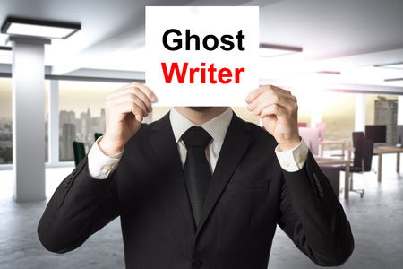 doctoral: businessman in black suit hiding face behind sign ghost writer