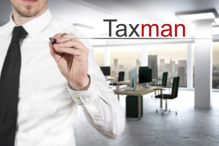 taxman: businessman in modern office writing taxman in the air Stock Photo