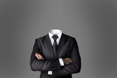 businessman without head crossed arms dark grey background 版權商用圖片