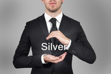 silver ingots: businessman in suit protecting word silver with hands