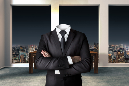headless businessman with crossed arms in modern urban office skyline Stock Photo