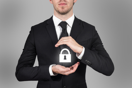 businessman in suit protects cloud lock symbol with his hands