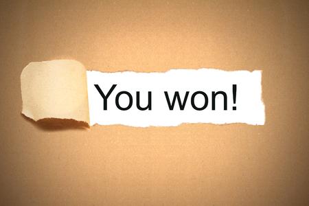 you won message brown paper envelope torn