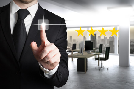 businessman in large modern office pushing virtual button four star review 版權商用圖片