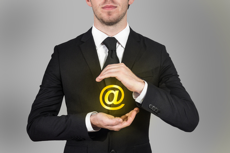 businessman in black suit protects internet email symbol with his hands  版權商用圖片