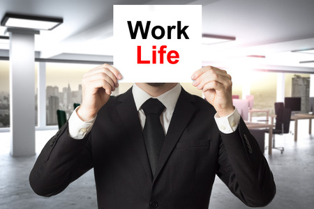 businessman in large modern office hiding his face behind sign work life balance 3d illustration