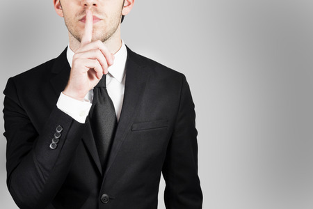 businessman in large clean office with finger on lips asking for silence 3d illustration Stock Photo