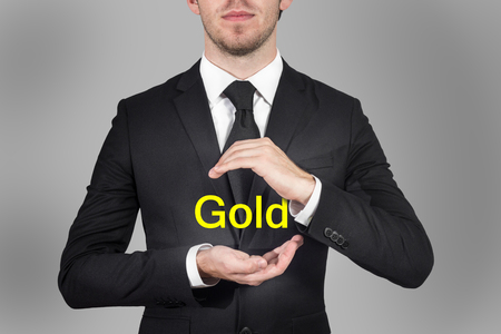 businessman in black suit protecting word gold with hands