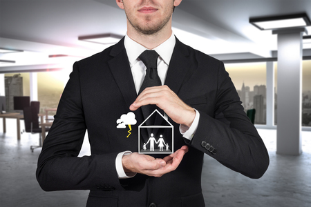 businessman protecting family standing in house with hands storm