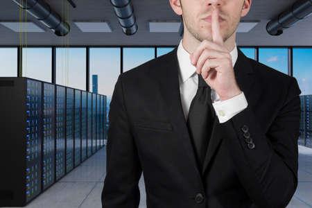 businessman in large server room with finger on lips asking for silence 3d illustration
