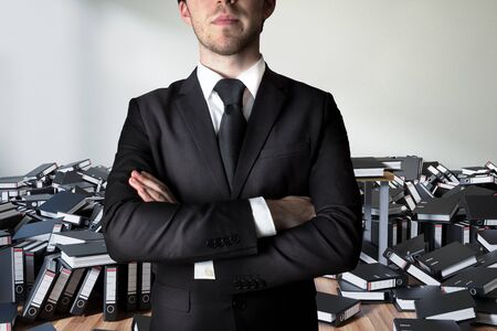 businessman crossed arms in front of a large pile of ring binders paperwork, conceptual burnout 3D Illustration Stockfoto - 131817270