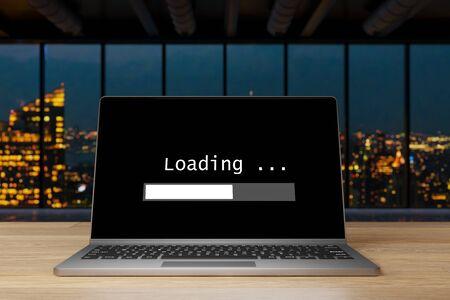 laptop on wooden desk in modern large indsutrial opffice at nighttime skyline view, loading screen progress bar, 3D Illustration Banco de Imagens