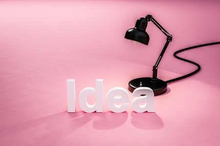 industry style desk lamp on pink colored surface with lettering idea; concept 3D online tutorial; 3D Illustration Stock Photo