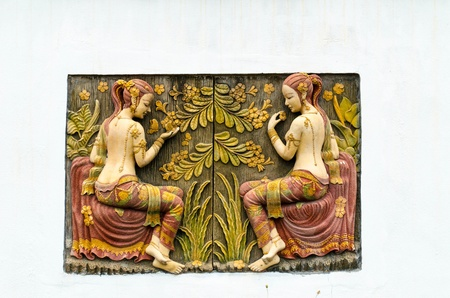 low relief: a beautiful bas relief of two girl with thai dress in a garden