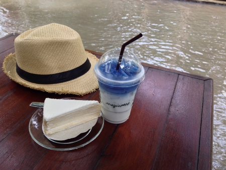 clothing: Hat, cake and drink on a table
