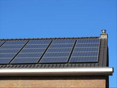 solar heating: Domestic Solar Panels  New solar panels on the roof of a family home with a background of blue sky