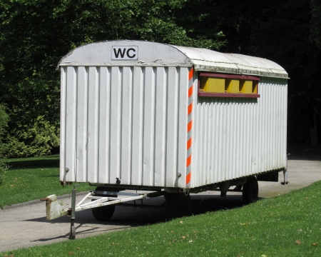 conveniences: Old Style Portable Toilet   An old fashioned wood constructed portable toilet block mounted on a trailer in an outdoors setting  Editorial