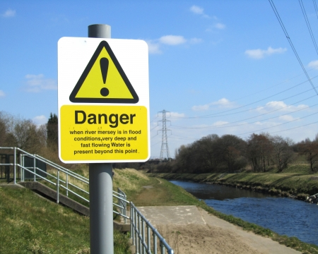 mersey: MANCHESTER, ENGLAND, APRIL 6: Warning sign next to the River Mersey in Didsbury, Manchester, England on April 6 2013. The sign is next to a sluice gate which is used to control water levels and prevent floods.                                 Editorial