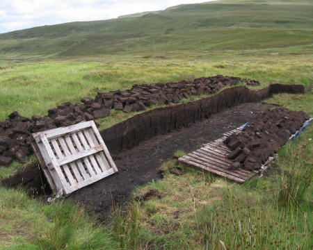 turba: Bloques de turba que se ha cortado de manera artesanal, en la isla de Skye en Escocia