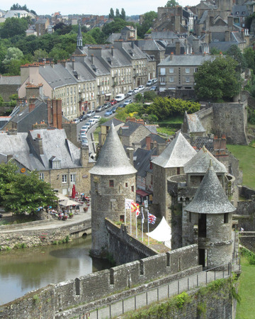 hugely: FOUGERES, FRANCE, JULY 13 2015: View of part of the castle and old town of Fougeres in Brittany. It is an old medieval town and a hugely popular tourist destination.