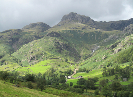 langdale pikes: Sun lights up a brooding Great Langdale Valley in the Cumbrian Lake District in England. With a stunning backdrop of the famous Langdale Pikes. Stock Photo