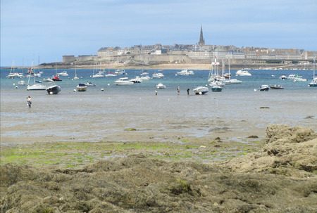 hugely: DINARD, FRANCE, JULY 20 2015: A view of the old walled town of St.Malo in Brittany in France, from the south west. St. Malo is a hugely popular vacation destination with thousands of tourists swelling is population each summer.