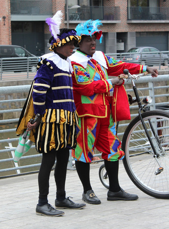 zwarte: AALST, BELGIUM, NOVEMBER 5 2016: Two colourfully dressed Zwarte Piets (Black Petes) during the arrival of Saint Martin at the Werf Quay in Aalst. Piet is the traditional helper of the Saint. Editorial
