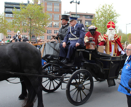 zwarte: AALST, BELGIUM, NOVEMBER 5 2016: Actor Anton Cogen, Commissaris Migrain from the Mega Mindy series, ridesin a horse drawn carriage with Saint Martin and Zwarte Piet in Aalst during the Saints parade