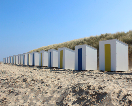 identical: A row of identical beach huts on a sandy beach at Cadzand Bad in Zeeuws-Vlaanderen in the far south west of the Netherlands. Stock Photo