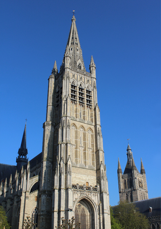 ypres: Exterior view of the beautiful St. Maartens Cathedral, in Ieper, Belgium, lit by the evening sun against a background of blue sky.