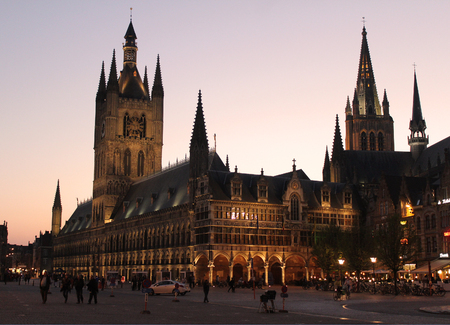 hugely: IEPER, BELGIUM, APRIL 8 2017: Sunset behind the beautiful landmarks of the Cloth Hall and St Martins church in Ieper. The town is a hugely popular tourist destination and a focus of war remembrance.