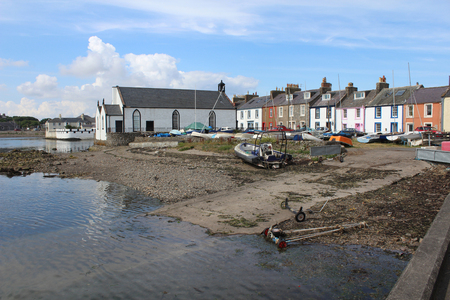 View of the pictureque harbour and surrounding buildings at the Isle of Whithorn in Dumfires and Galloway in Scotland. One of the most southerly ports in Scotland. Редакционное