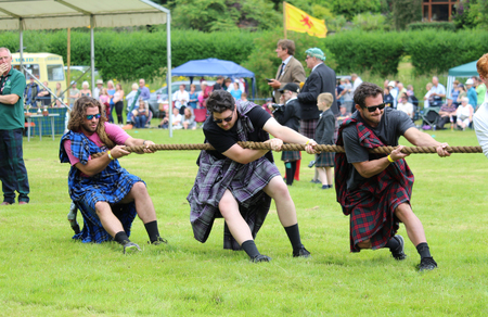 CRIEFF, SCOTLAND, 21 JULY 2018: Members of the public take part in the 'Tug of War' event at the Lochearnhead Highland Games near Crieff in Scotland. An annual event promoting Highland culture and traditions. Editorial