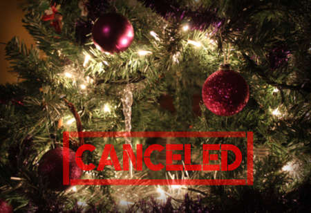 Red 'Canceled' text on a blurred decorated Christmas tree background with copyspace. Holiday season canceled concept due to Corona virus or other reasons.