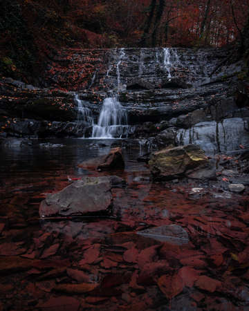 Beautiful mystic waterfalls in autumn season. View on the stream around the stones. Colorful cascade of water and red leaves around. Фото со стока