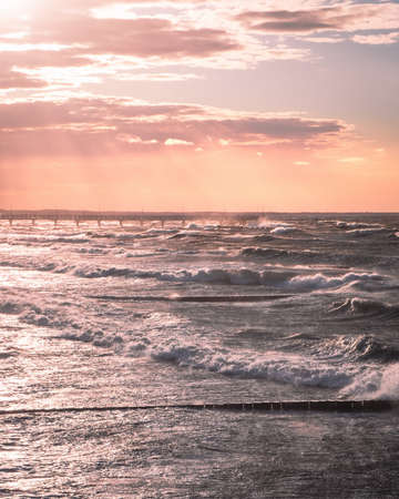 Beautiful pastel sunset with view on the pier and sea waves. Pink sky and dramatic water waves. Relaxing landscape. Photo of Baltic sea.
