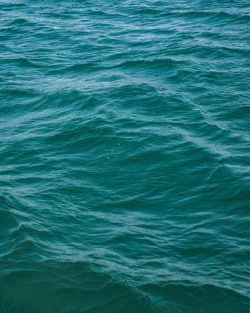 Beautiful sea water background. Cerulean color of the water. Marine surface, fresh and clean turquoise flow. Shiny blue ocean texture.
