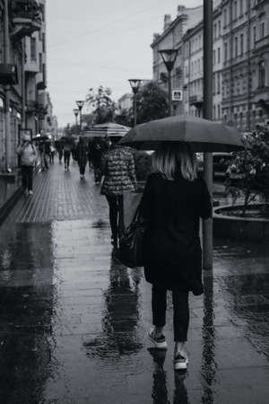 People walking with umbrellas under the autumn rain. Black and white photo of rainy wet weather in city. Urban life. Фото со стока