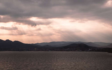 Photography of the sunset on the lake. Orange reflection on the water, mountains in the background. Dramatic view, breathtaking seascape. Golden sun rays. Фото со стока