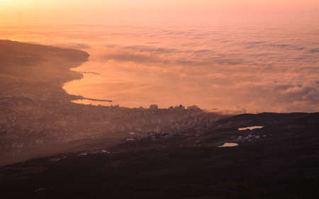 Beautiful sunrise with clouds above the sea. View from the mountain on the town. Peaceful scenery, inspiring nature.