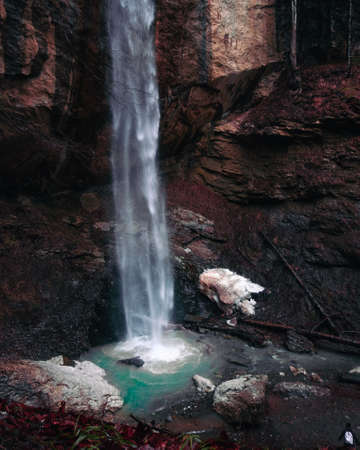 Beautiful mystic waterfall in autumn season. View on the stream falling down the cliff. Colorful giant cascade of water and person standing and watching at it. Фото со стока