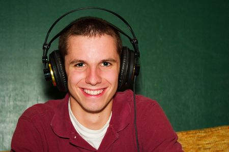 A Guy wearing headphones smiling.