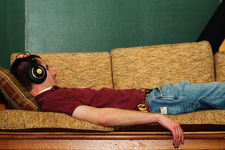 A guy lying on a couch listening to music.